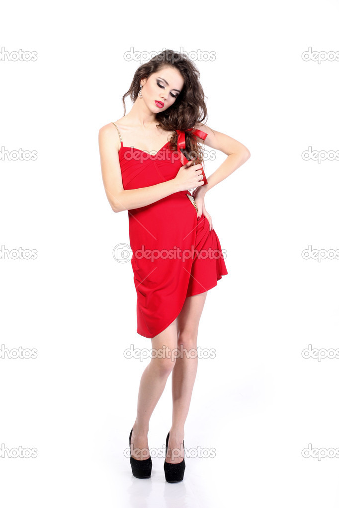 Attractive young woman in red dress posing on white background