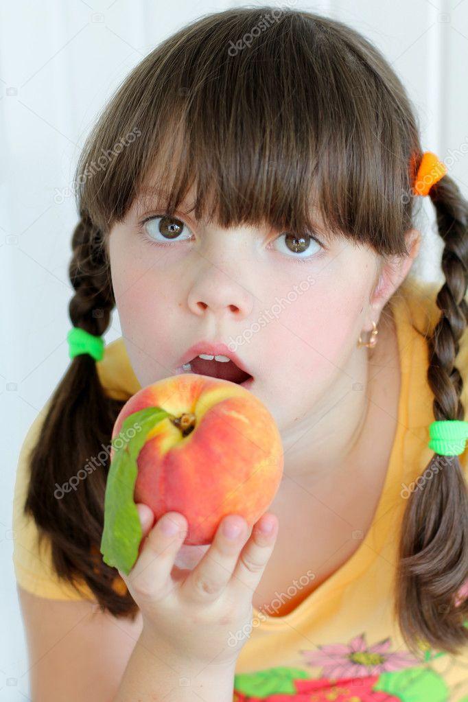 young beautiful girl eating orange peach stock photo