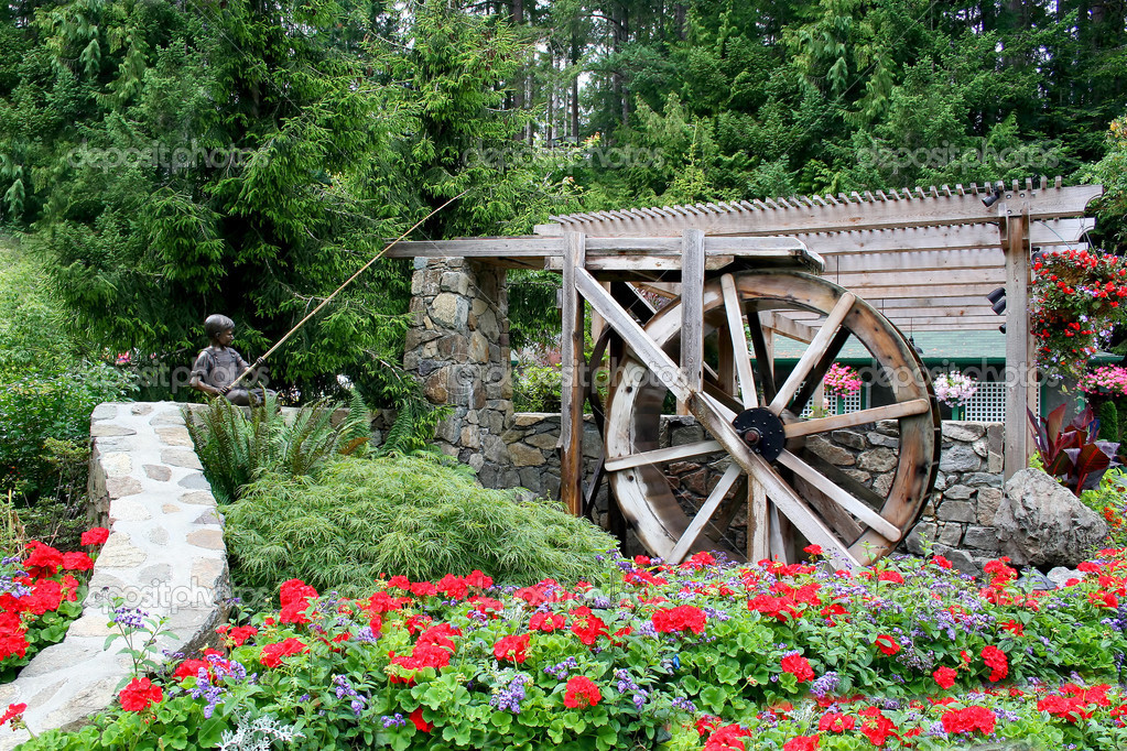 Beautiful Springtime Flower Garden And Waterwheel Sculpture. U2014 Photo By  Coffee999