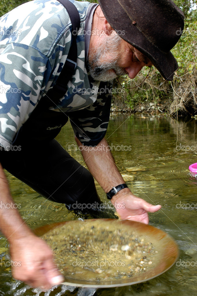 Prospector panning for gold in river