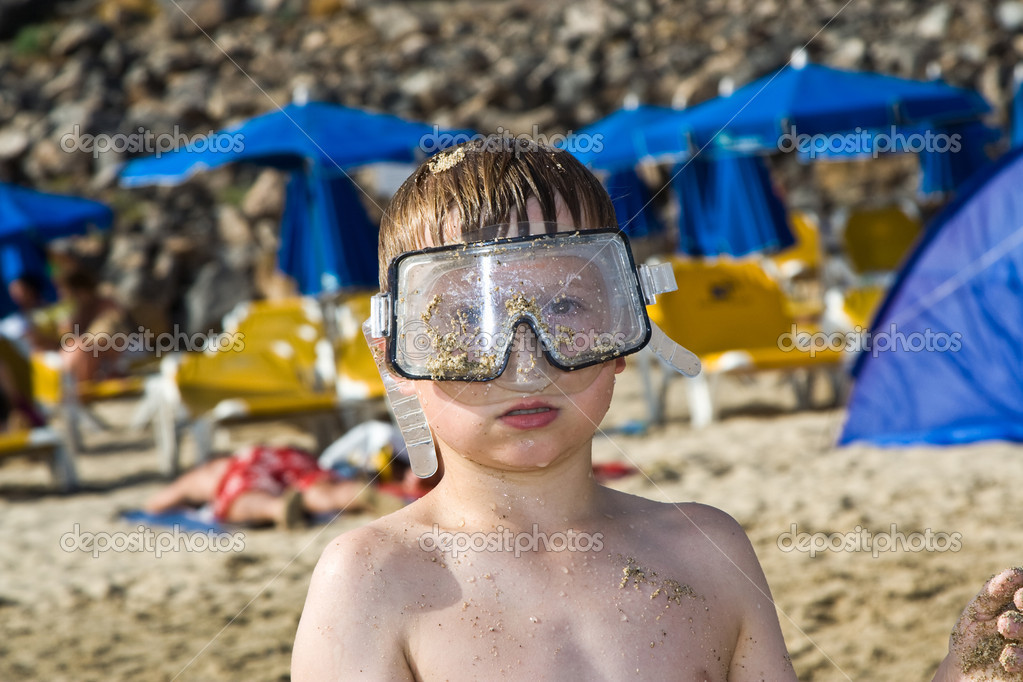 Child, boy with diving goggles is playing intensively at the sandy beach