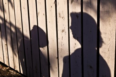 Shadow of a boy with mother at a wooden fence