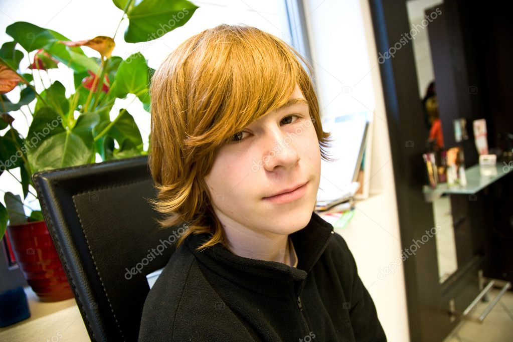 Boy with long red hair at the hairdresser