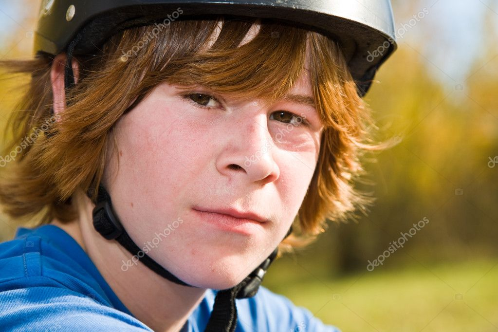 Boy with red long hair and helmet rides on a dirtbike and looks