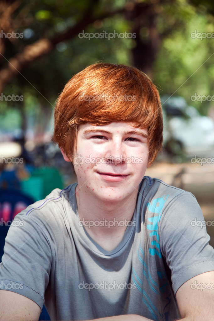 Boy with red hair and pickax in the face looks happy
