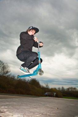 Boy riding a scooter and going airborne on a scooter park