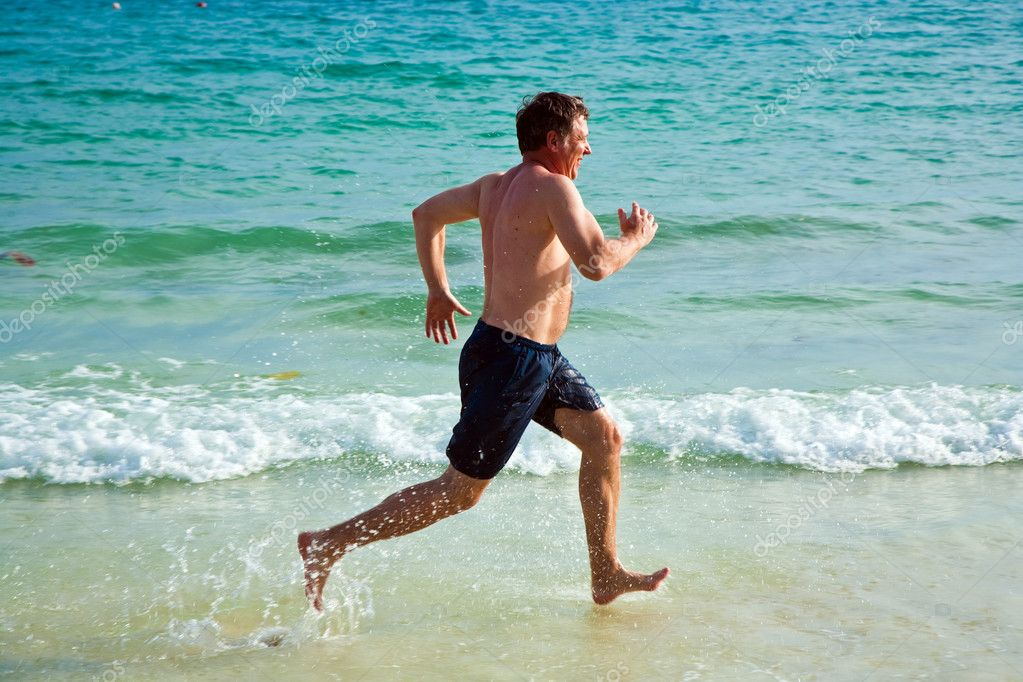 Man is running along the beautiful beach