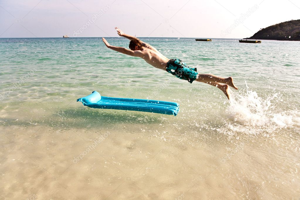 Young boy with red hair in swimsuit is running along the beautif
