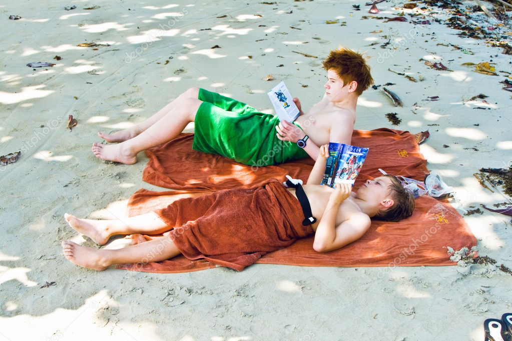 Brothers are lying at the sandy beach in the shadow, relaxing an