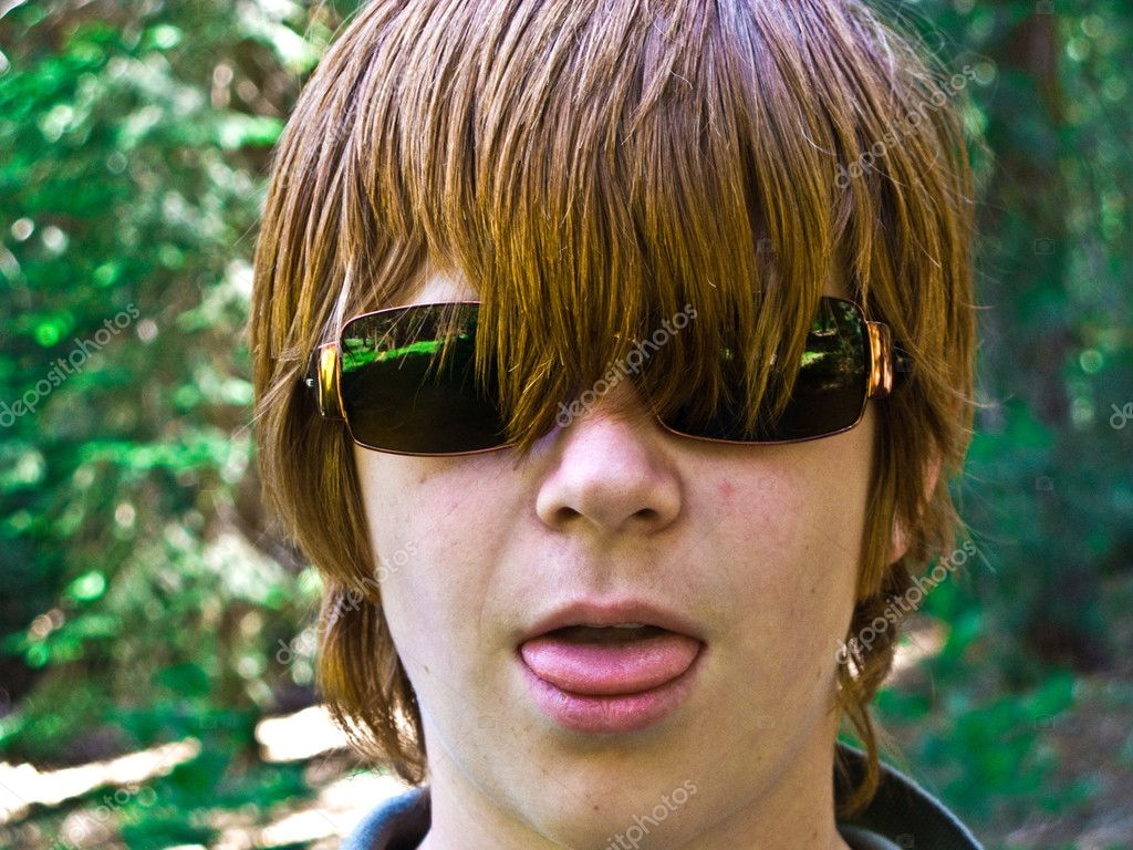 Young boy with red long hair and sunglasses pocks his tongue and looks real