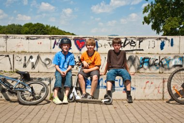 Three friends relaxing and sitting on a concrete bench at the skate park