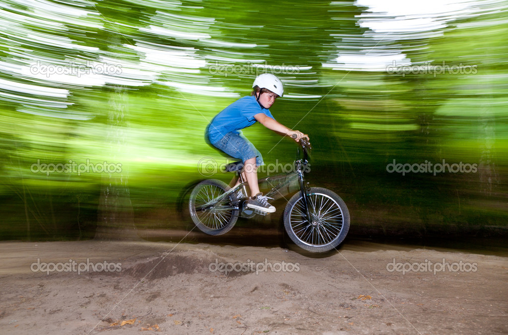 Child has fun jumping with the bike over a ramp