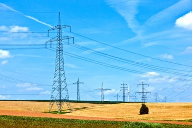 Electrical power line with wind generator in rural landscape