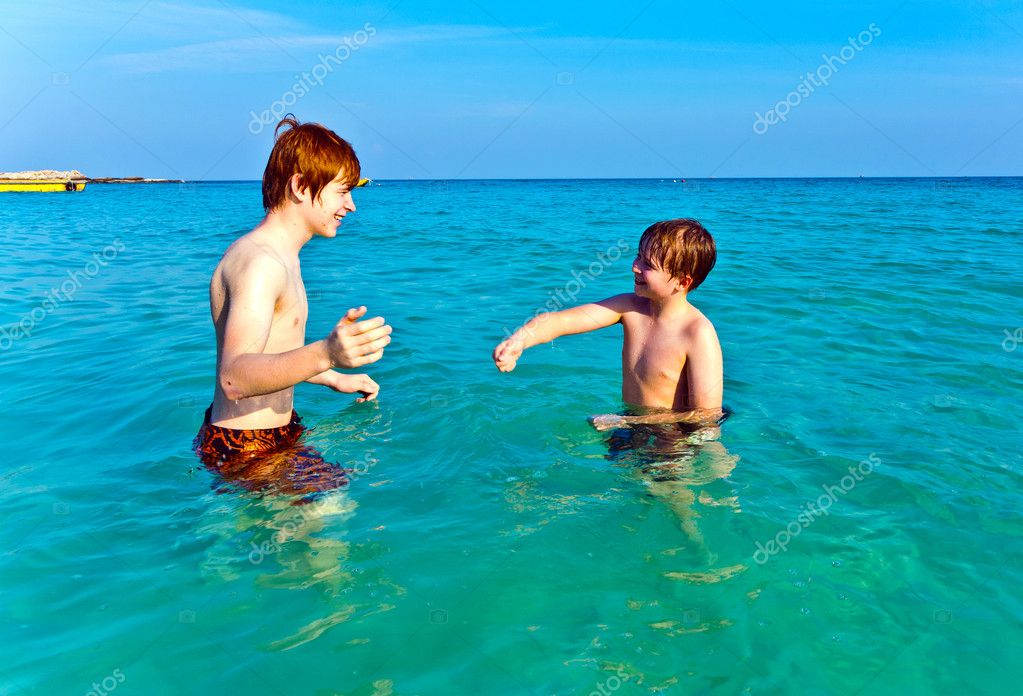Brothers are enjoying the clear warm water at the beautiful beach