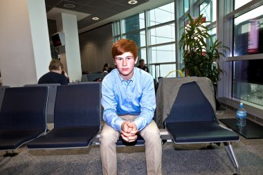 Boy waiting in the gate at the airport for the call of boarding