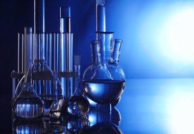 Laboratory flasks on turn blue background