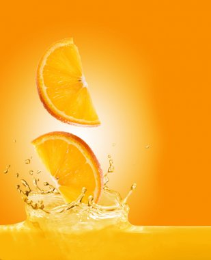 Orange slices fall in juice