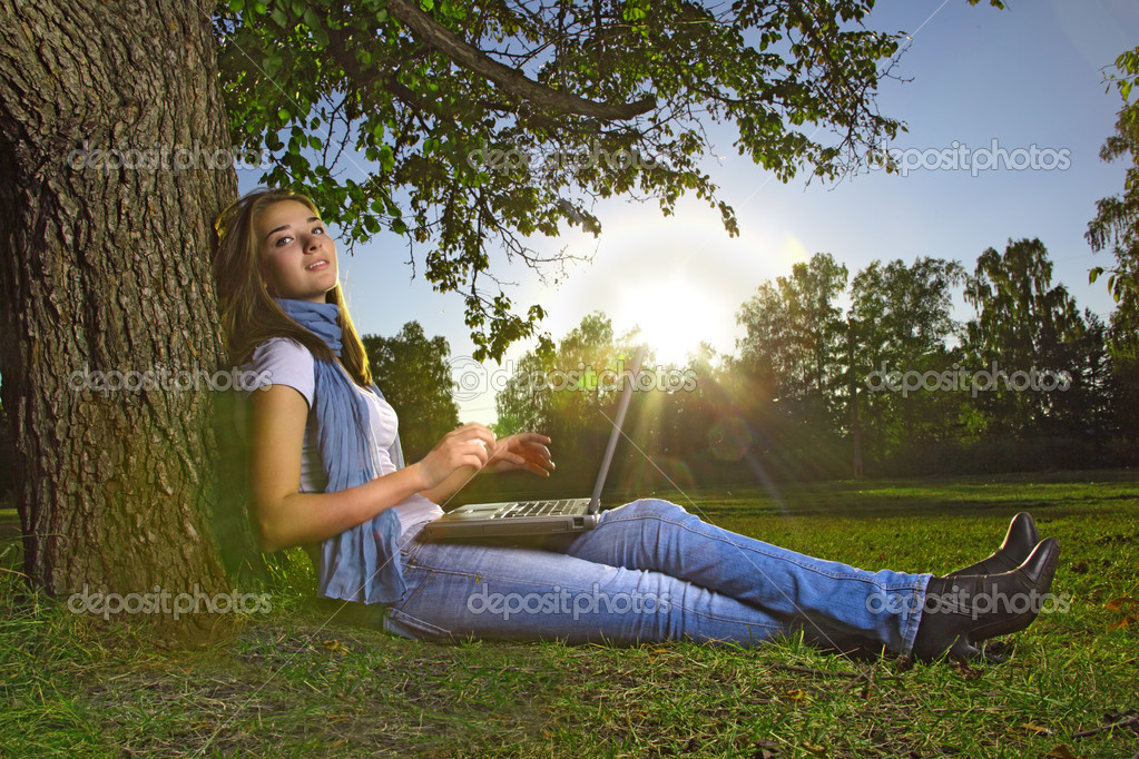 Beauty girl with laptop in park