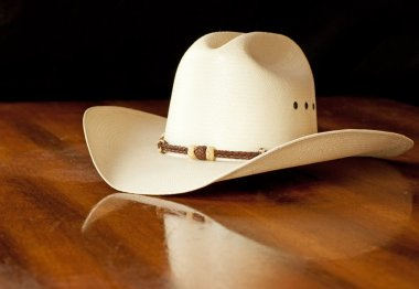 White straw cowboy hat with a hatband on a wooden table