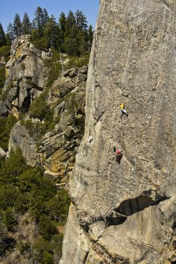 Tema of climbers ascending a steep rock face