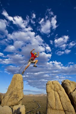 Male rock climber leaps across a gap on the summit of a pinnacle with a cloud filled sky behind hiim. stock vector