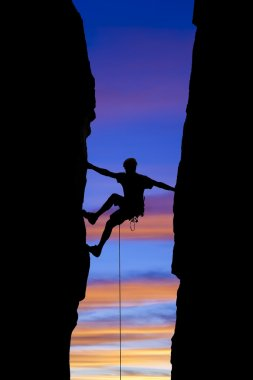 Rock climber reaching across a gap.