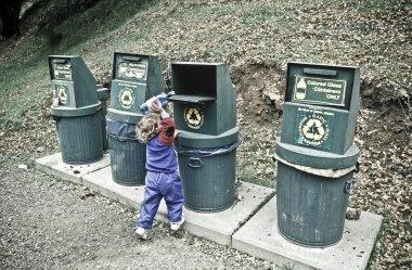 Little girl recycles plastic bottle.
