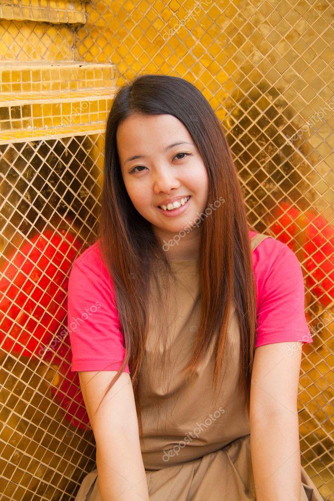 Thailändische Frauen sitzen und lächeln mit goldenen
