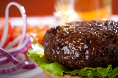 Beef burger with onion and beer on background