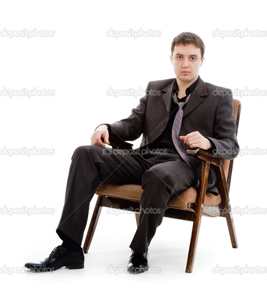 a young man in a suit and tie sitting in a chair stock photo 5652494. Black Bedroom Furniture Sets. Home Design Ideas