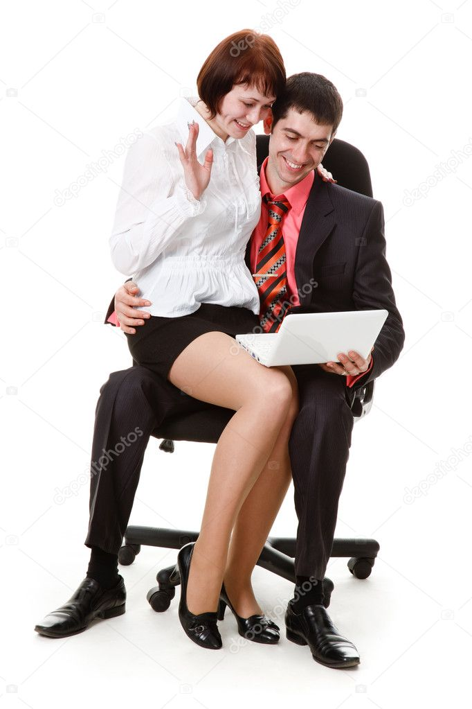 young man and woman sitting in a chair looking at laptop stock photo 5707257. Black Bedroom Furniture Sets. Home Design Ideas