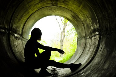 Silhouette of a young girl smoking in sewer pipe