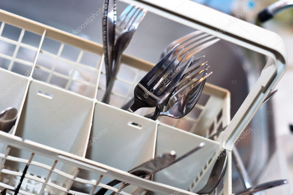 forks and knives in washing machine with blurry background stock