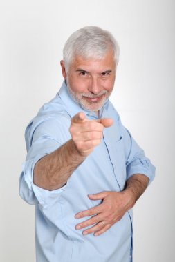 Smiling senior man pointing at camera