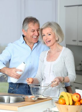Senior couple in kitchen baking cake