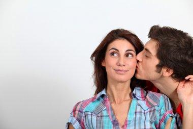 Young man kissing girlfriend on cheek