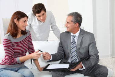 Young couple sigining renting contract