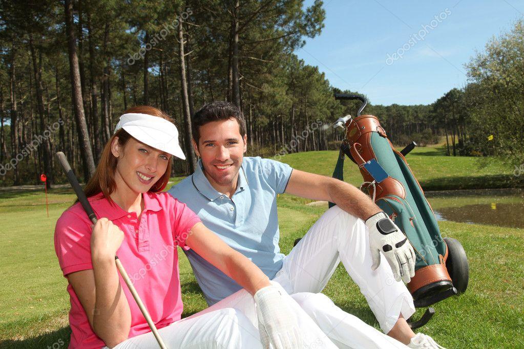 Couple sitting on a golfcourse