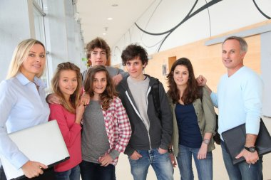 Portrait of teenagers and teachers standing on school hall