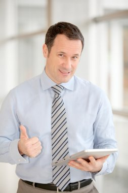 Businessman standing in hall with electronic tab