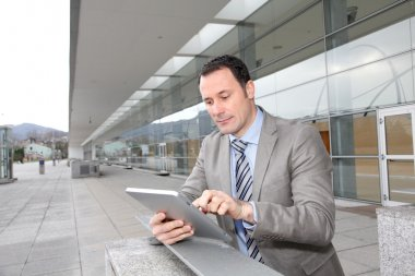 Businessman using electronic tab outside congress center