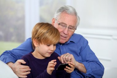 Old man with little boy playing video game on telephone