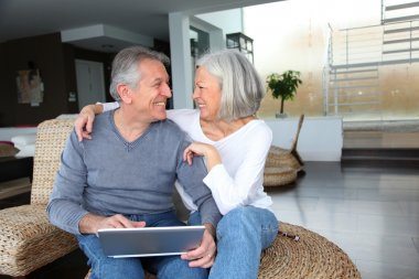 Happy senior couple connected on internet at home