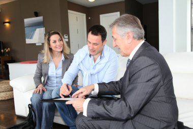 Couple with real-estate agent signing home investment contract