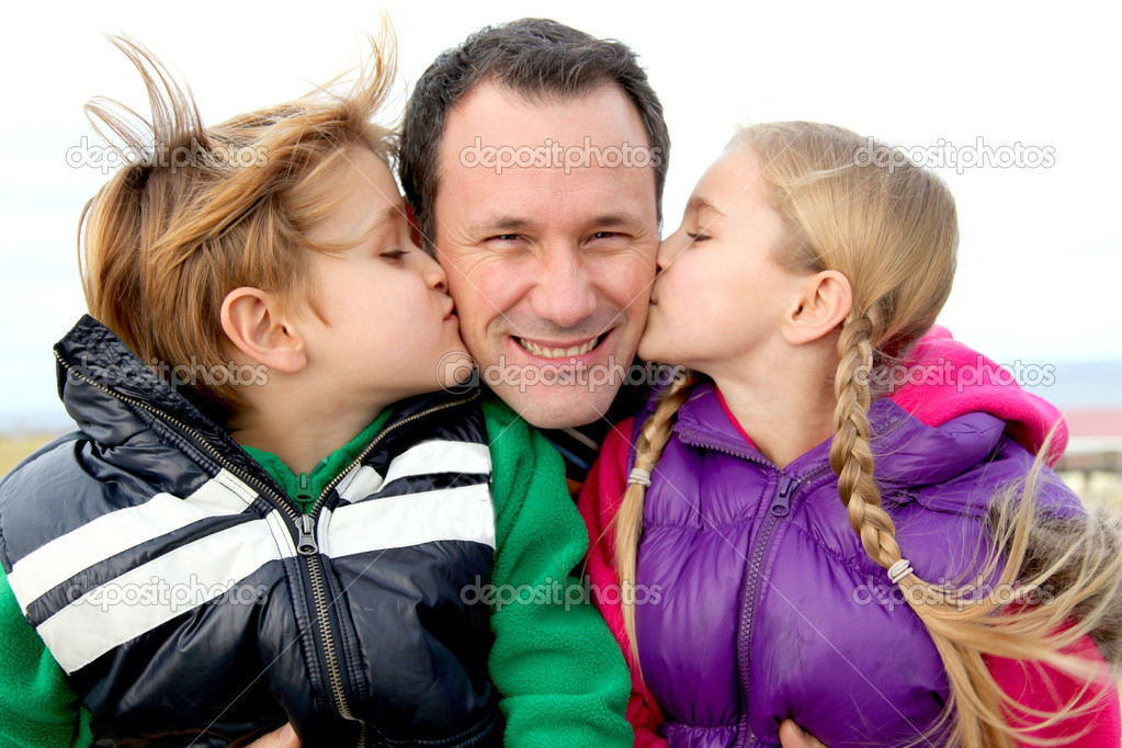 Kids giving a kiss to their daddy