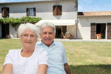 Senior couple sitting in front of a house