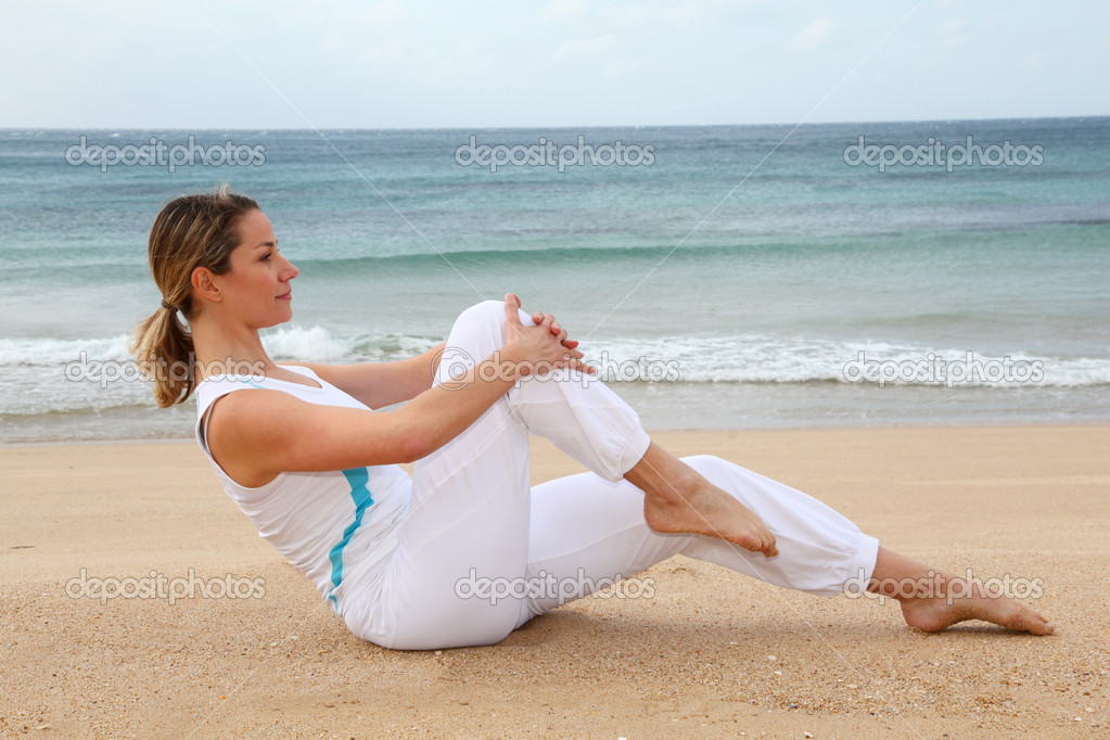 Woman doing stretching exercises at the beach