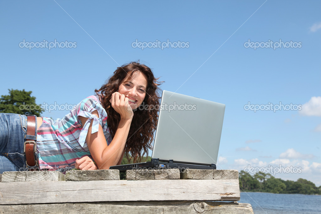 Woman with laptop on a pontoon