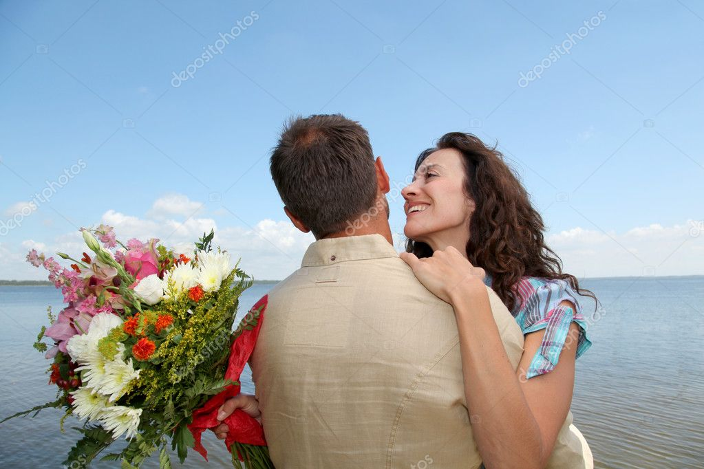 Loving couple with bunch of flowers