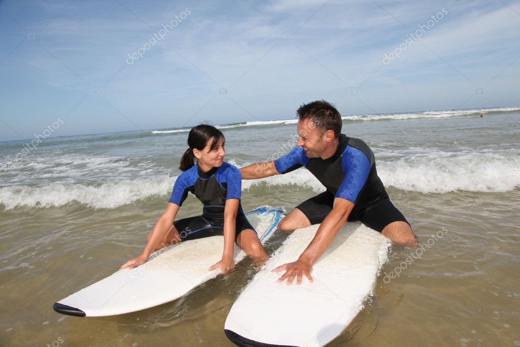 Father and daughter surfing